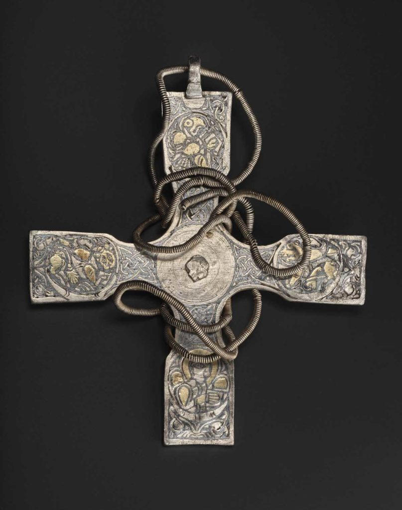 a decorated Christian cross with wire necklace entwined around it
