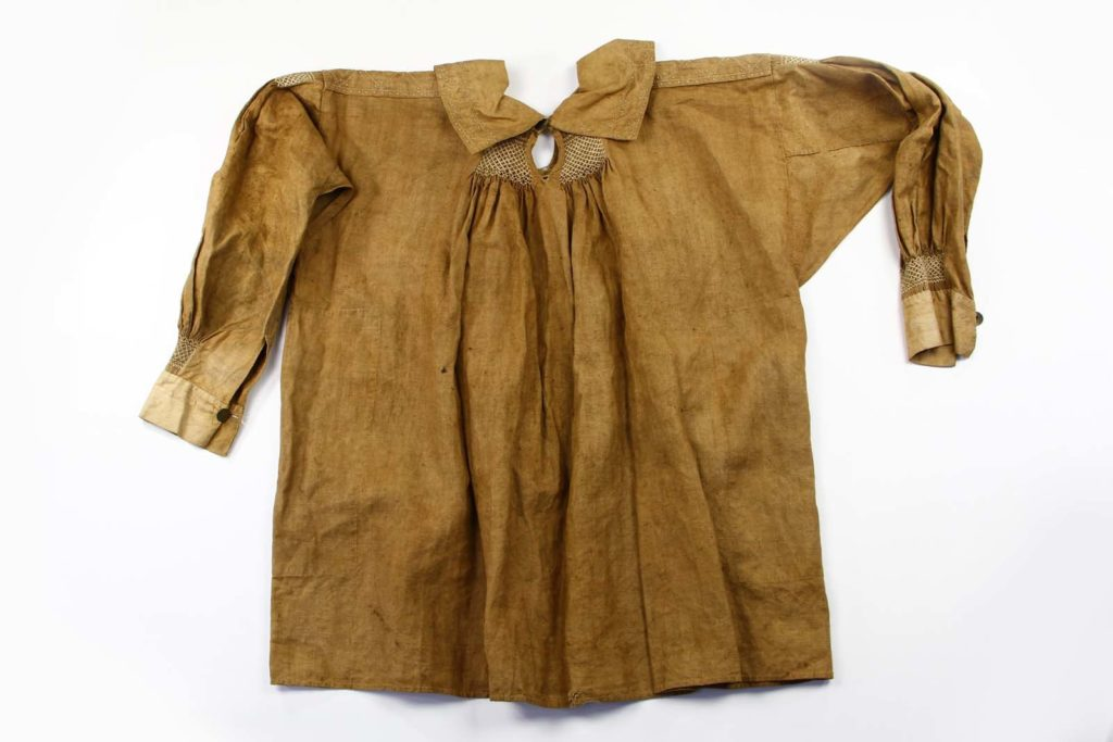 photograph of a brown linen garment with long sleeves, collar and embroidery around the neck