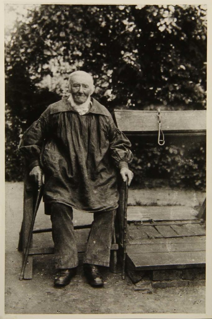 old black and white photo of an elderly man with white hair and beard wearing a smock whilst seated on a bench