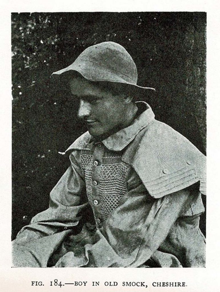 black and white photo of a young man wearing a smock with large collars