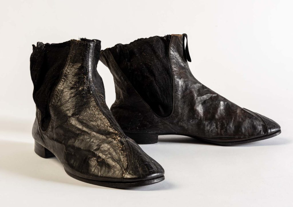 a pair of well worn black chelsea boots with elasticated sides