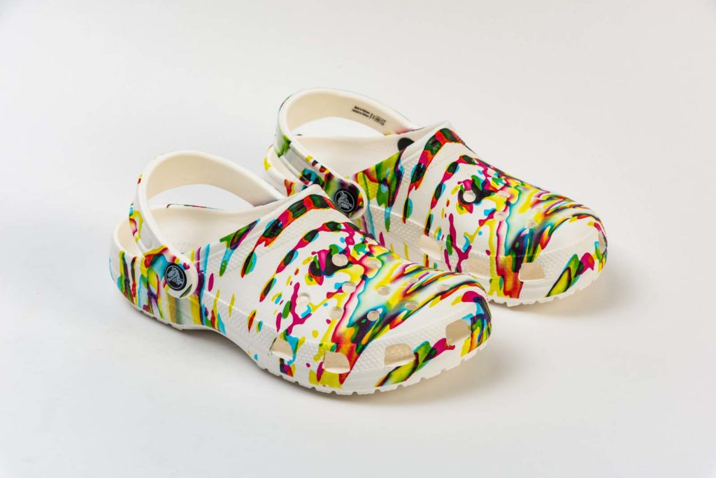 photo of a pair of crocs with splatter paint pattern design