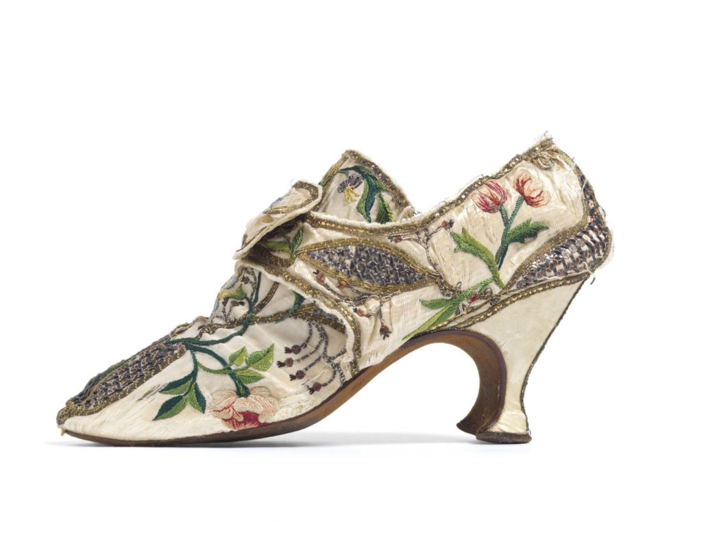 photo of a high heel shoe with a cream floral pattern