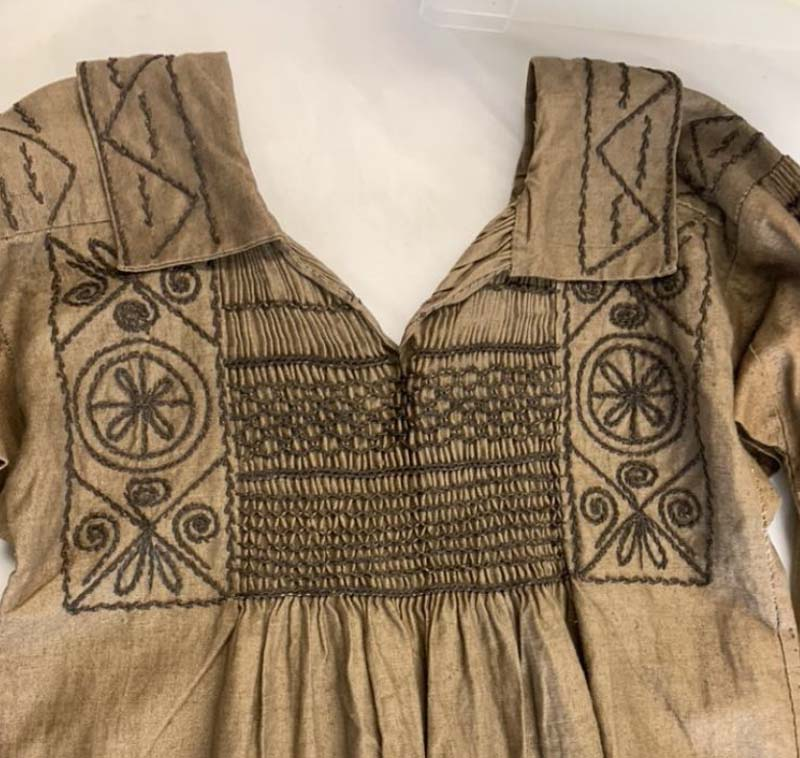detail of embroidery around the collar of a brown linen shirt like garment with open collar
