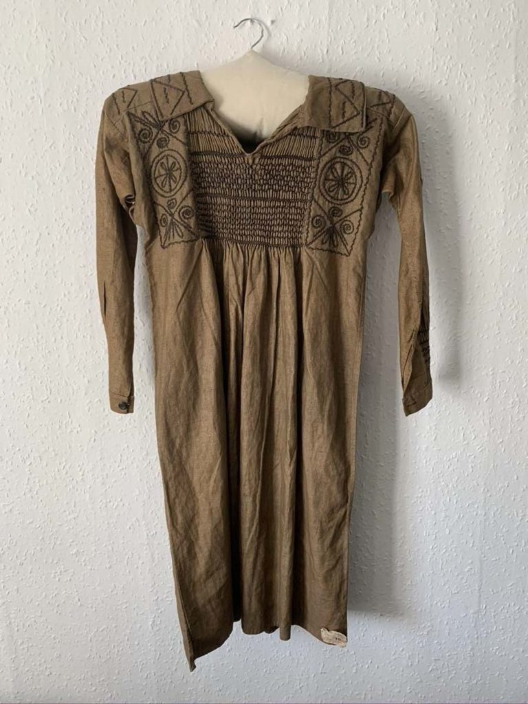 photo of a long linen one piece over shirt type garment in brown linen with embroidery around the collar