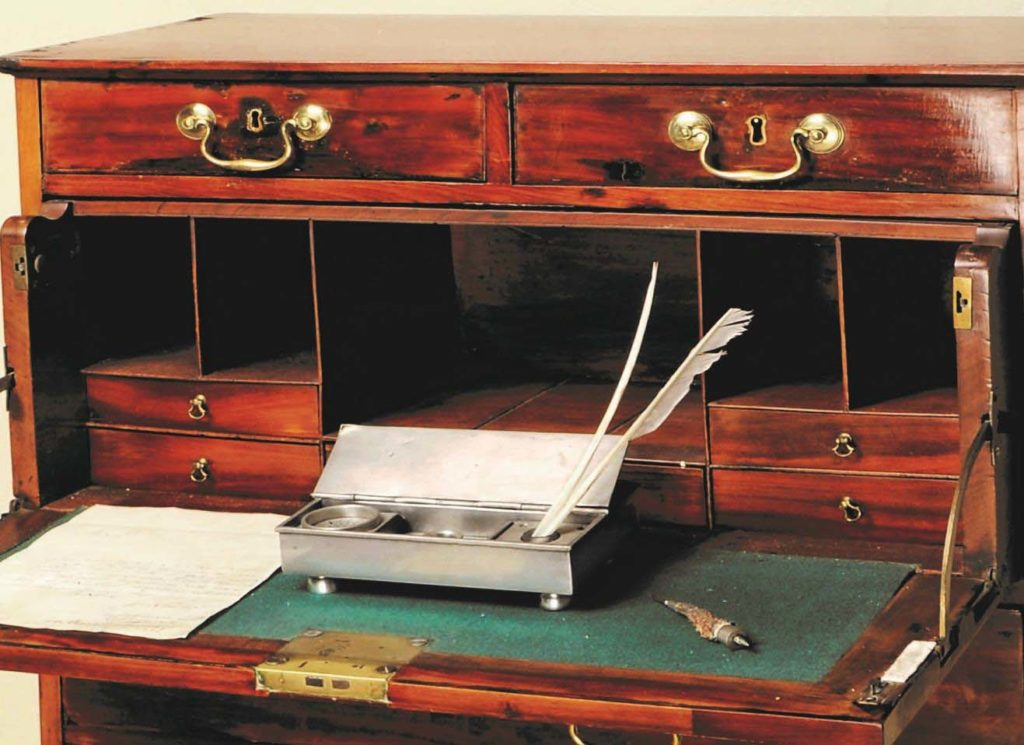 close up of a desk showing lowered writing surface, interior drawers and quill and ink stand