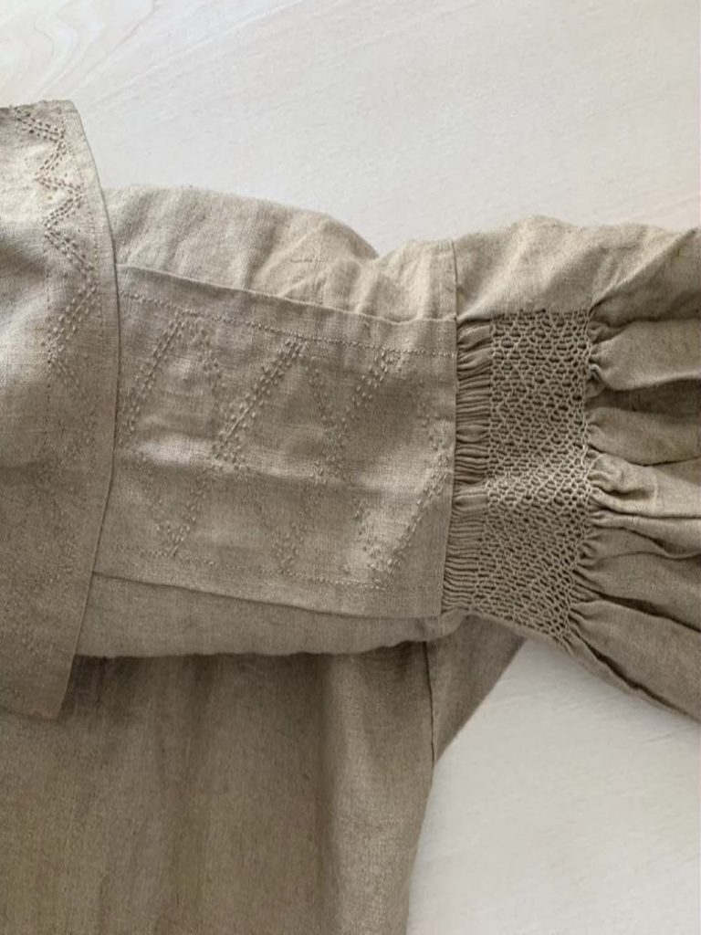 detail photo of embroidery on the arm of a smock