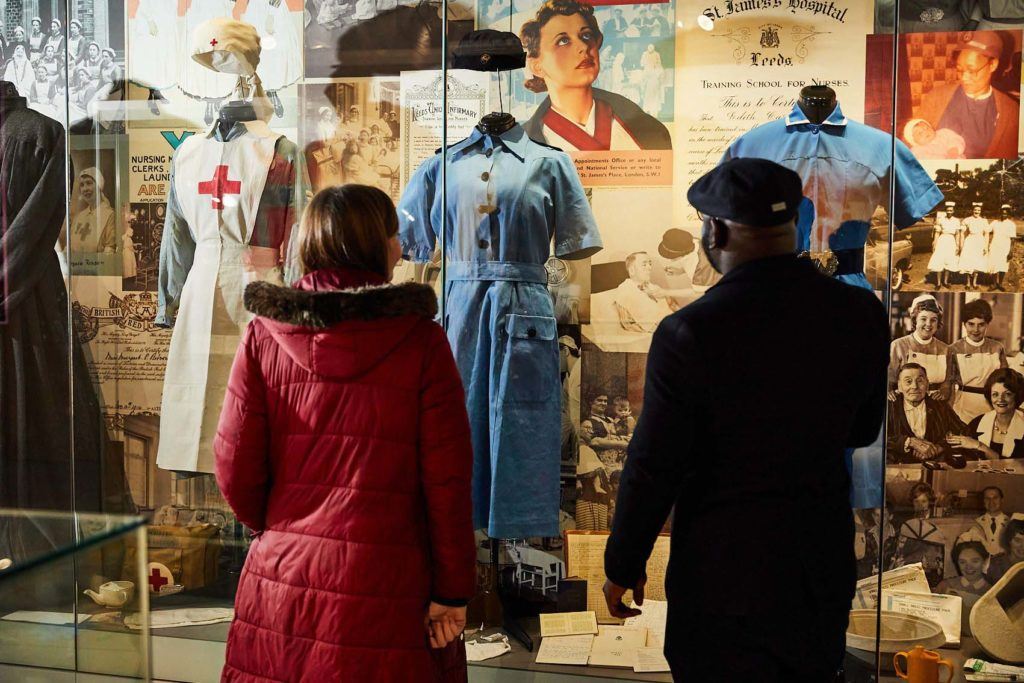 photo of two peope looking at a display case of nurses uniforms