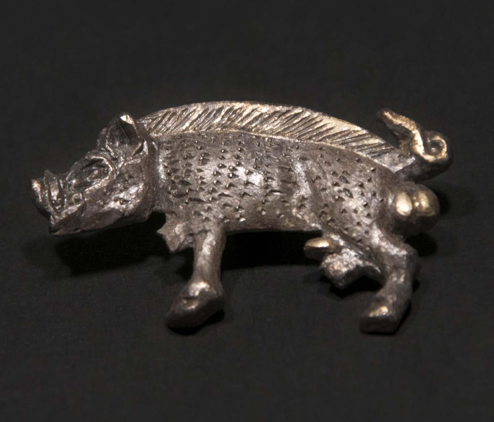 small pendant in silver in the shape of a boar