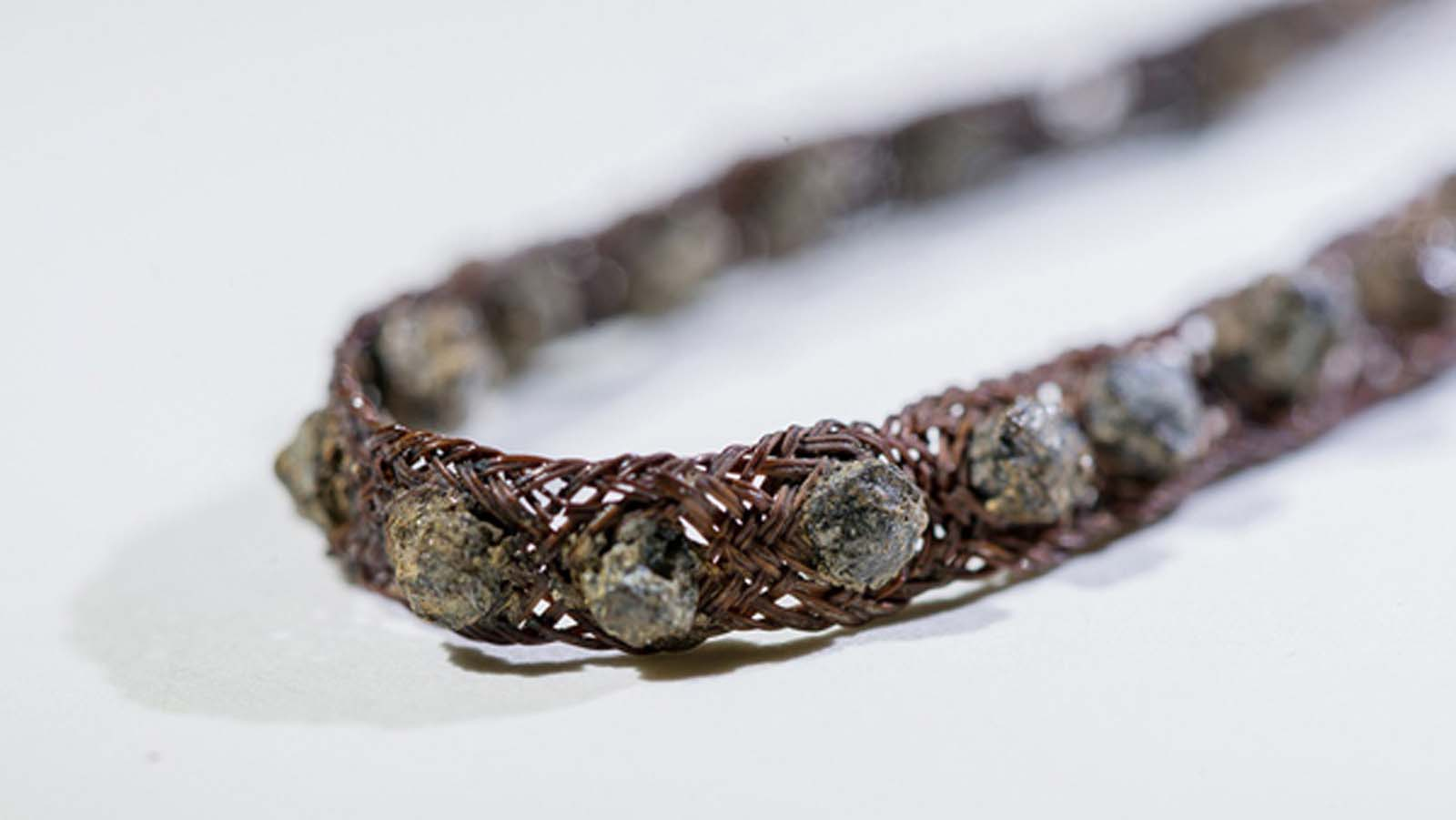 close up of fragile bracelet made of bronze and precious stones