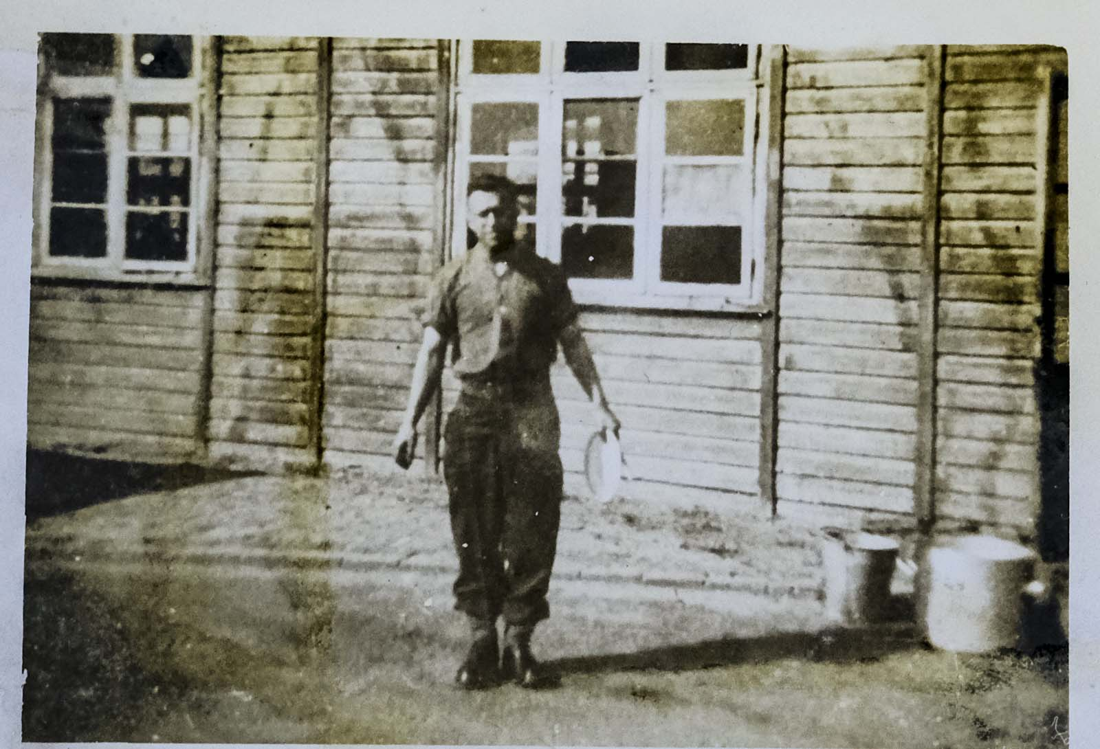 photo of a soldier in his shirt sleeves outside a hut