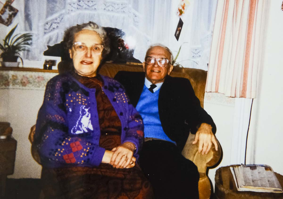 photo of an older couple sat together in an arm chair