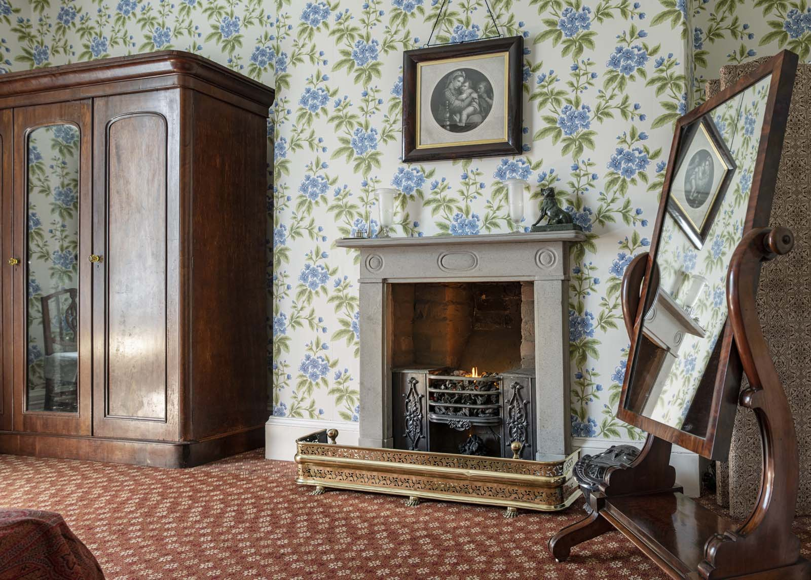 photo of a Victorian bedroom fireplace with floral wallpaper and teak wardrobe
