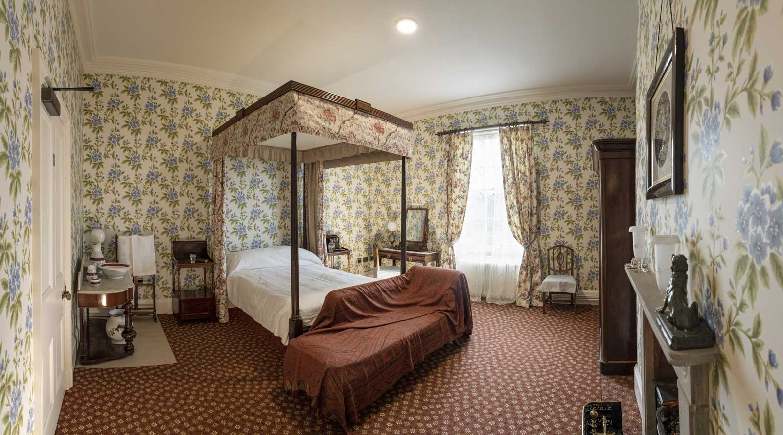 photo of a Victorian style bedroom with four poster bed and floral wallpaper
