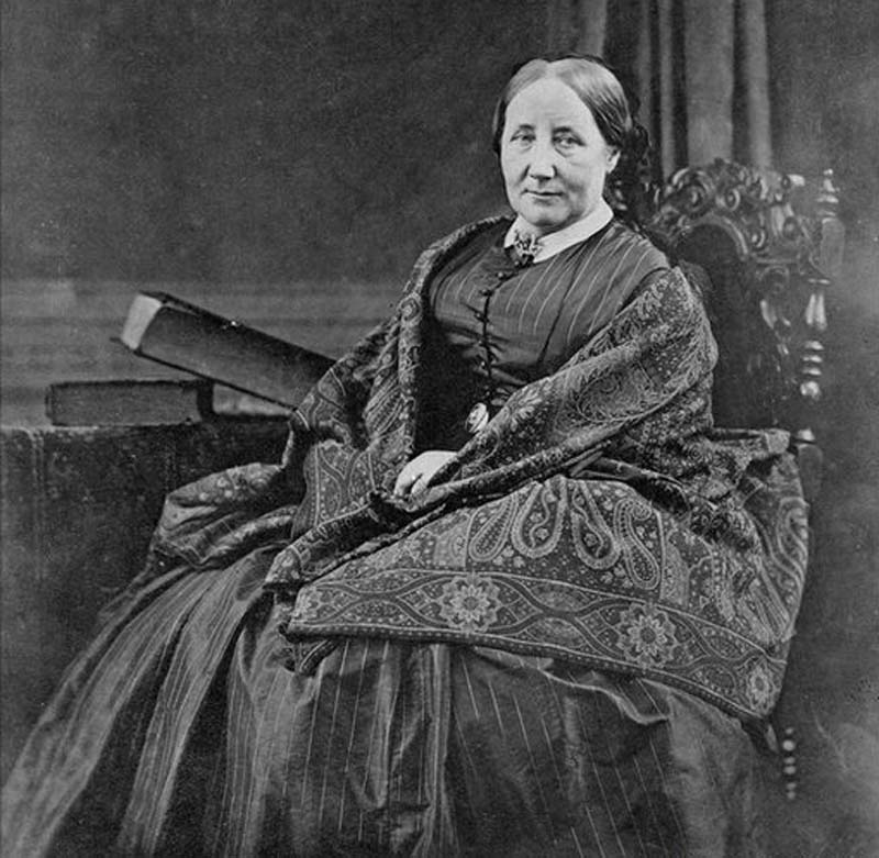 black and white photo of a seated woman in shawl and large Victorian dress