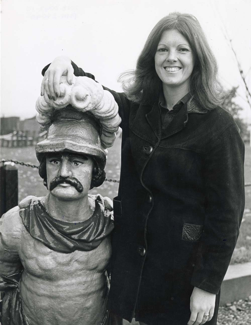black and white photo of a woman with long hair posing with a ships figurehead
