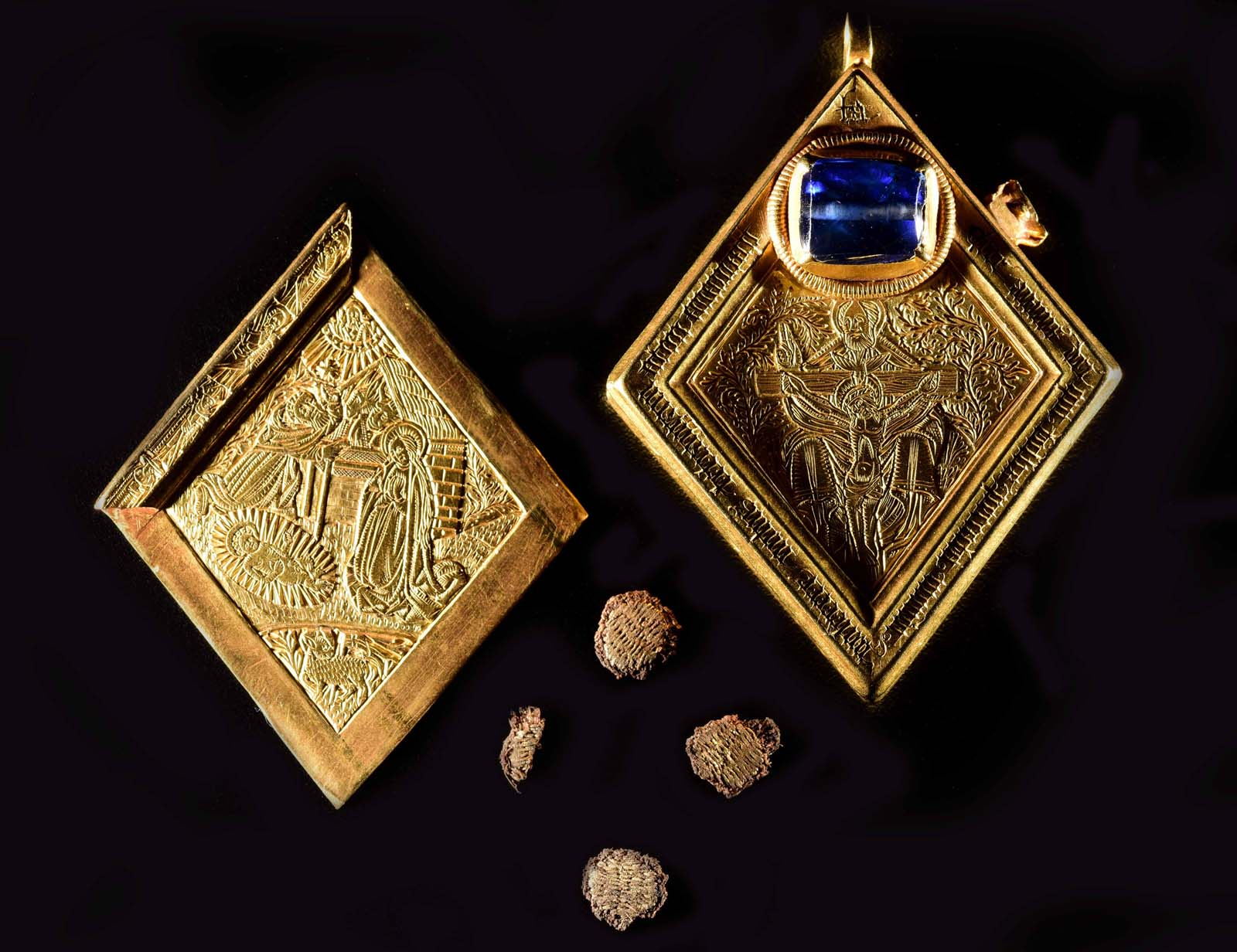 two golden trapezoid-shaped jewels with interior engraving detail
