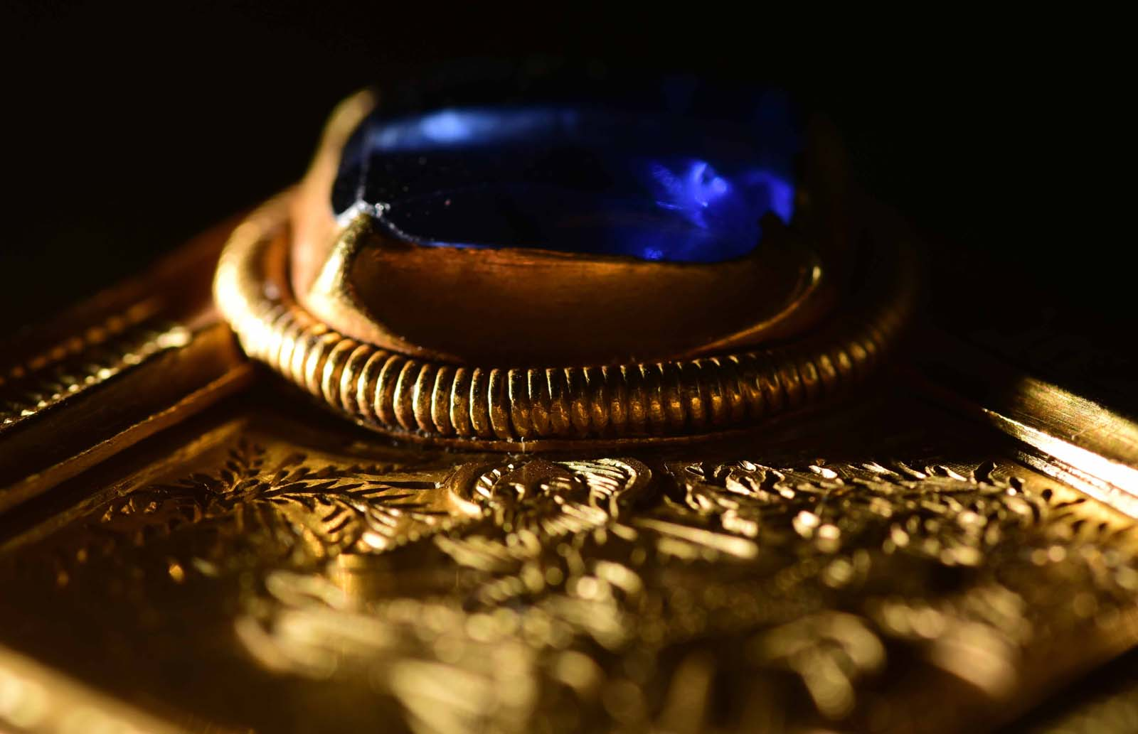 close up photo of a blue jewel set in gold mount