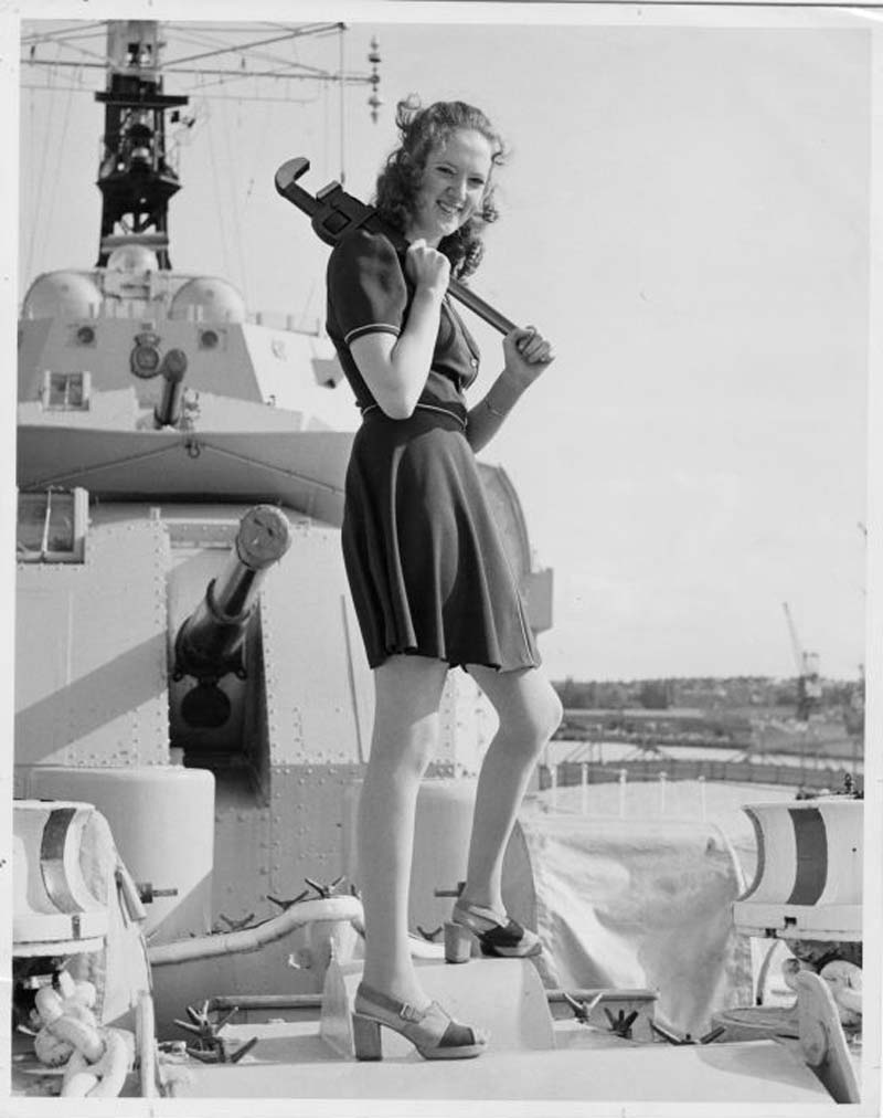 photo of a woman in a short dress holding a large wrench on the deck of a ship