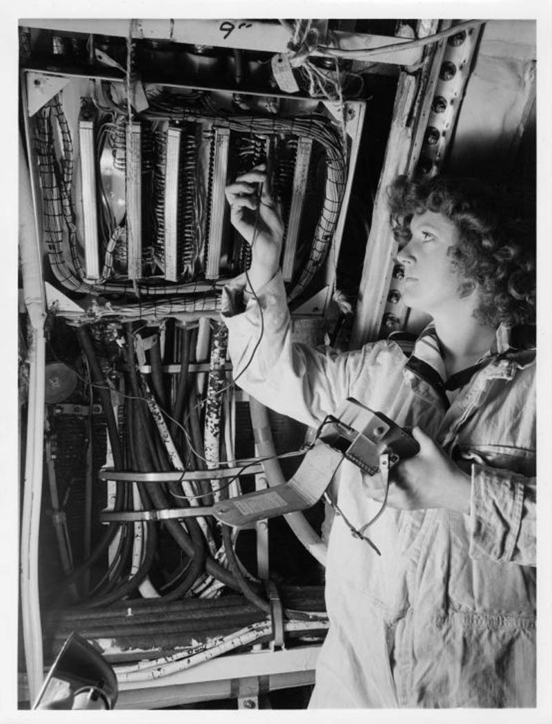 photo of a woman inspecting circuit board wires