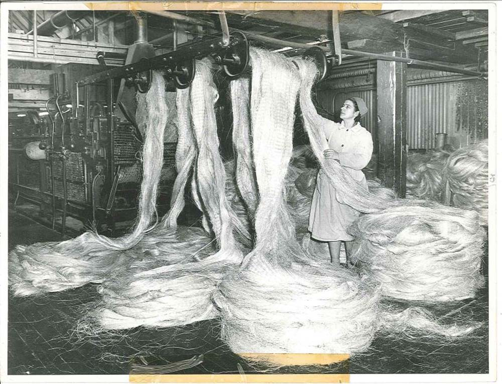 photo of a woman working with alrge swathes of rope twine bundled and stretches across rafters