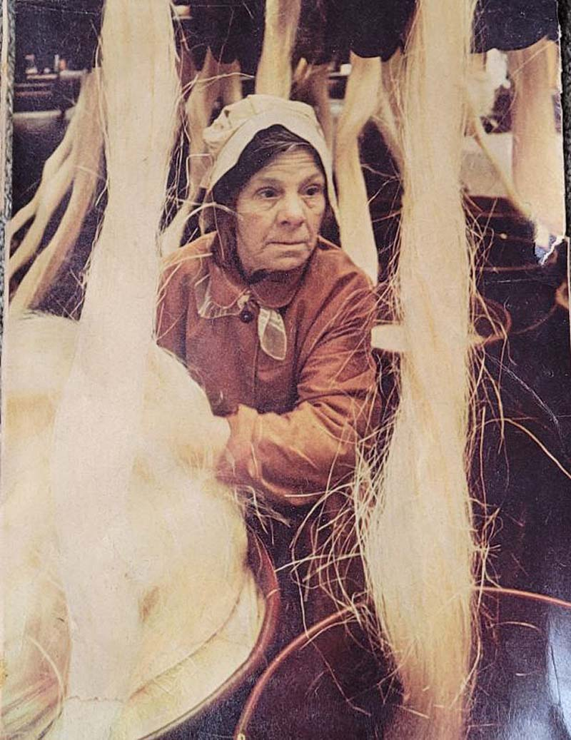 colour photo of a woman surroinded by bundles of rope twine