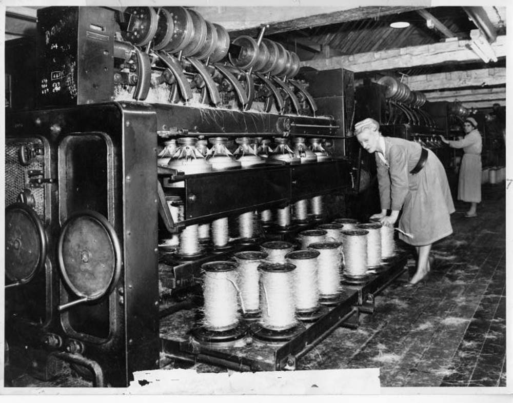 photo of a woman with a series of large spinning bobbins on a machine