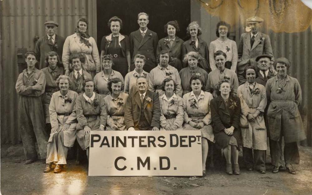 group portrait of mena nd women workers with sign saying Painters Dept. C.M.D