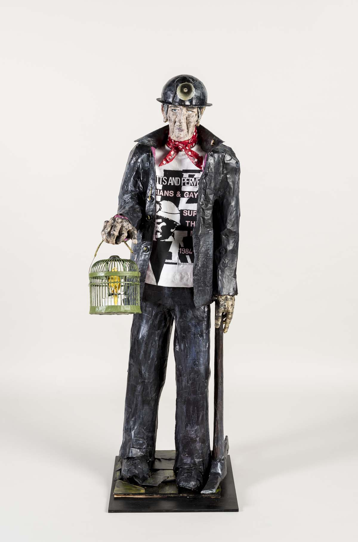 model of a coal miner carrying a canary in a cage and wearing a Gay rights t-shirt