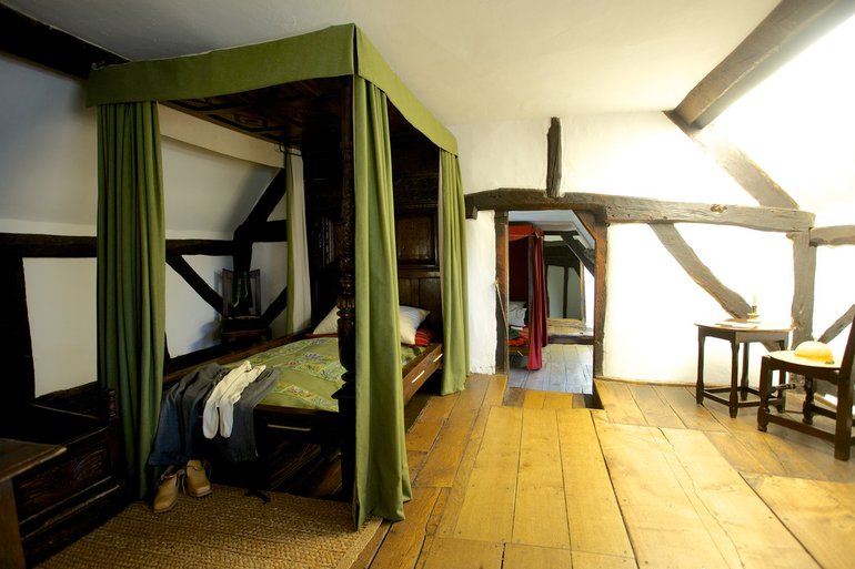 interior shot of a cottgae bedroom with beams and four poster bed