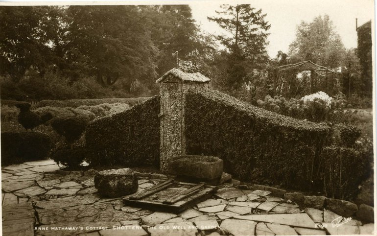 black and white photo of hedges and a well in a paved garden area