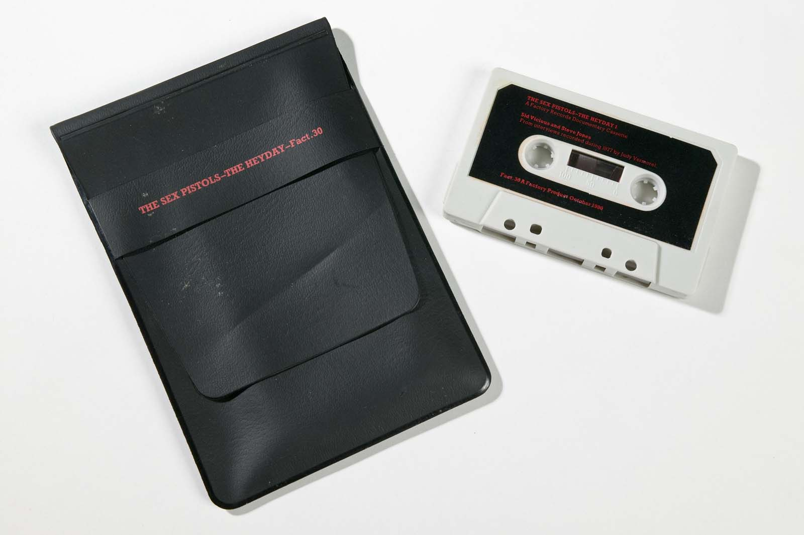 photo of an audio cassette next to balck holder for it