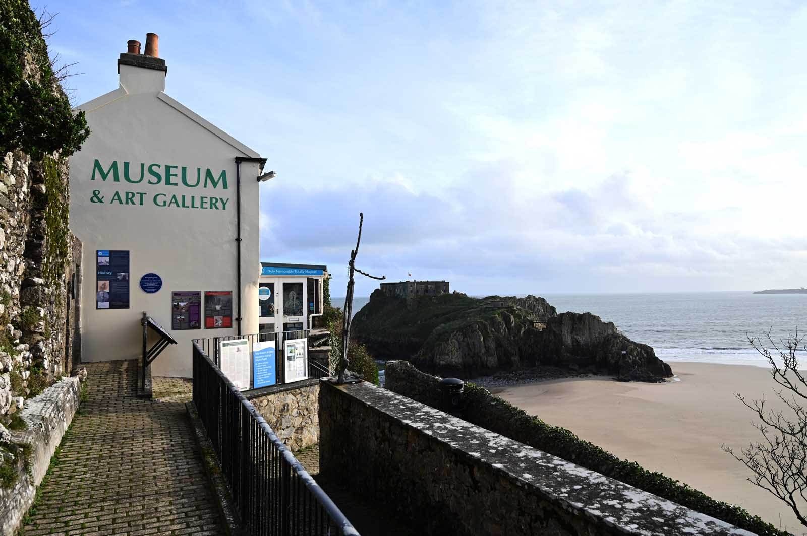 view of Tenby Museum and Art Gallery - two storied whitewashed building with chimney and gable end overlooking a beach cove with rock outcrop and castle in the distance