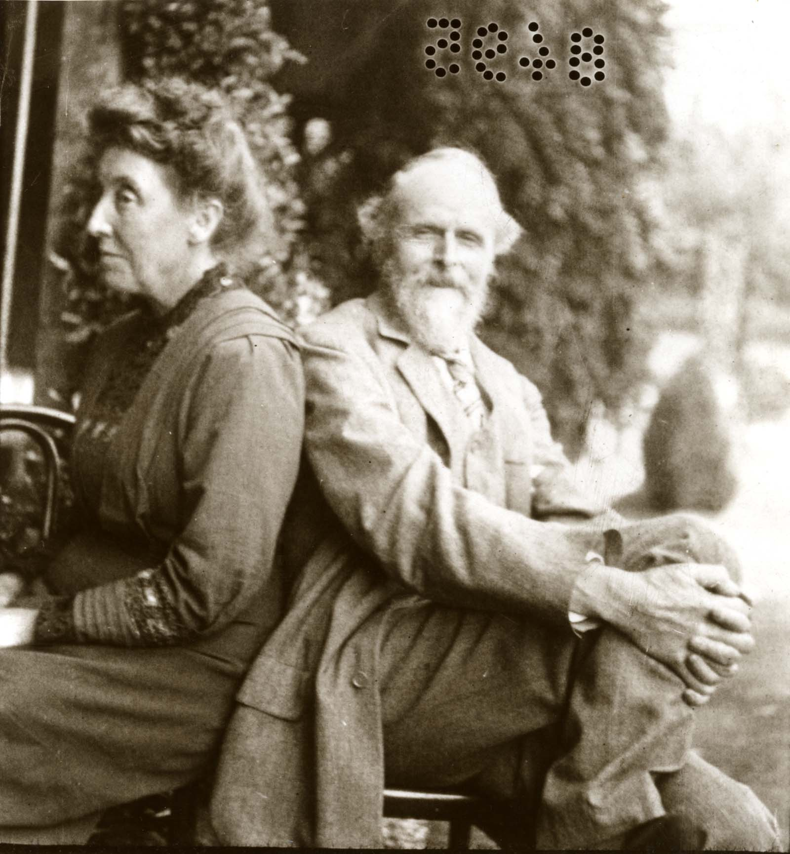 blck and white photo of a Victorian man and woman seated back to back on a bench in a garden