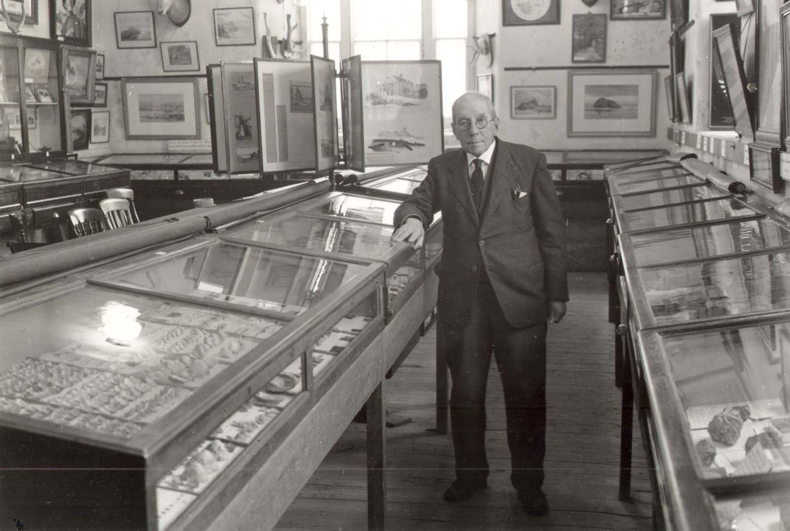 black and white photo of a man in amuseum gallery filled with display cases