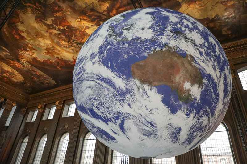 giant 3D model of Earth in large room with ornate painted ceiling