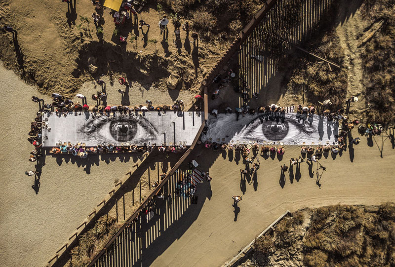 large scale artwork of eyes held by crowd of people in the desert