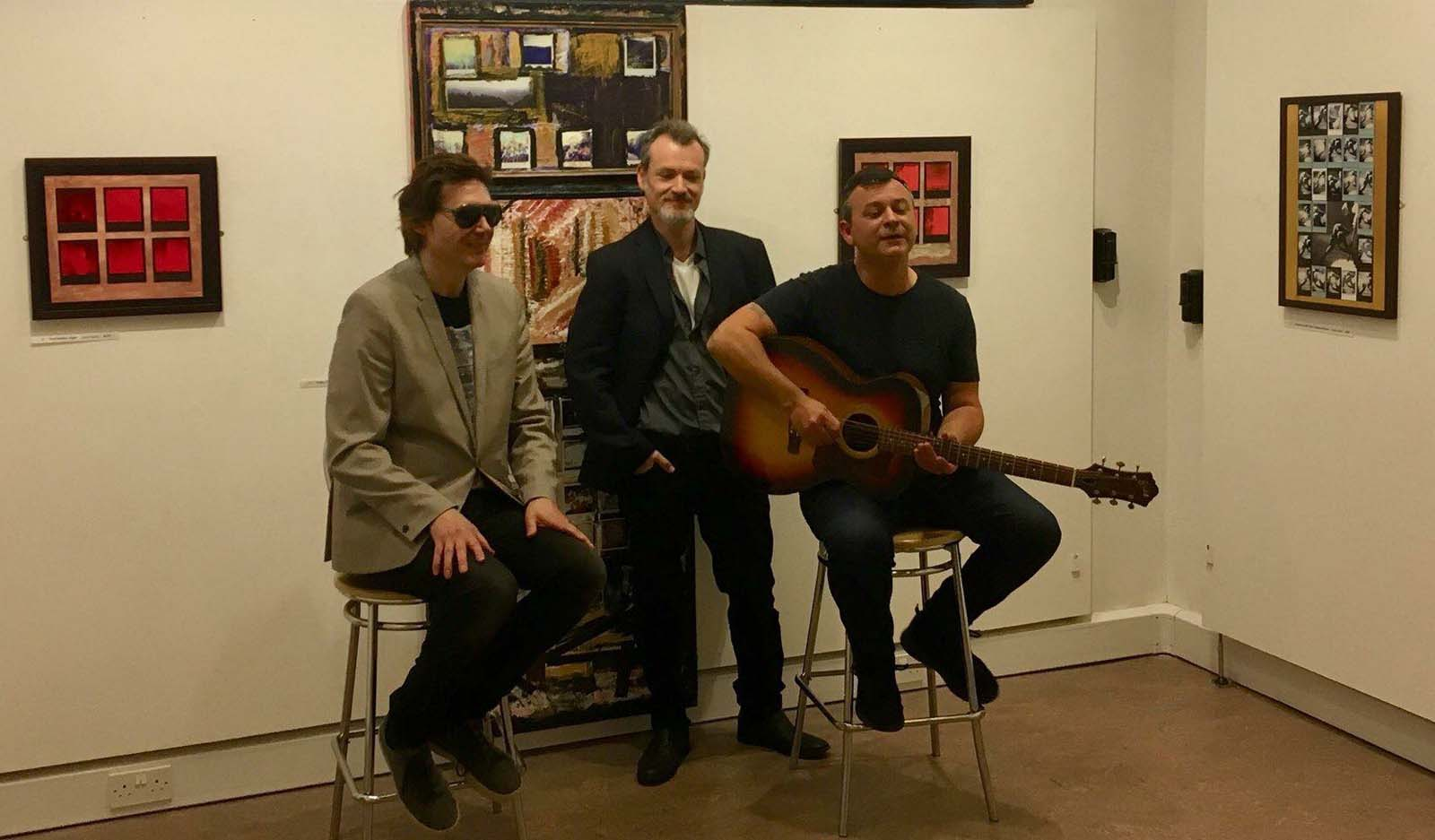 photo of three men in a gallery two of them seated and one of them holding a guitar and singing
