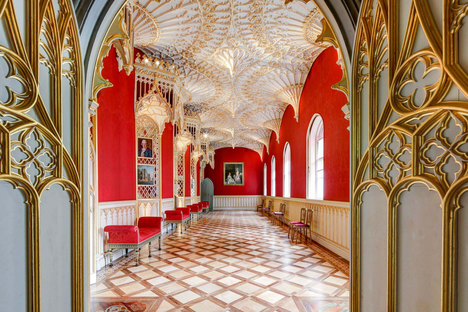 photo of a long rococo room with gilded ceiling, red walls and gothic window arches