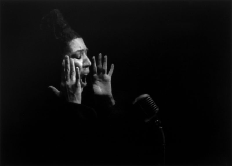 woman singing into a microphone through darkness