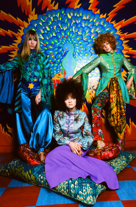 three models wearing bright 1960s clothing in front of psychedelic peacock wall art