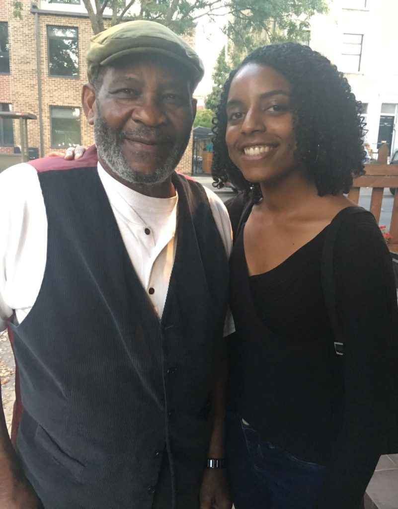 photo of a young woman with an older man wearing a waistcoat and flat cap