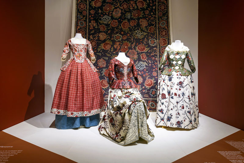 three dresses made from chintz fabric on display in museum gallery