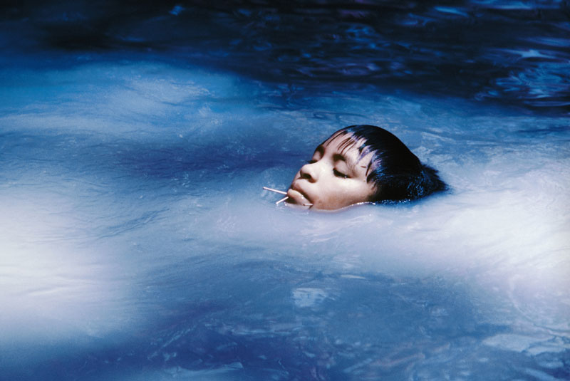 child floating in body of water, with just their face visible
