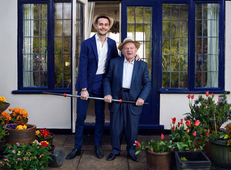young man and older man in doorway wearing blue suits and holding a barbell bar