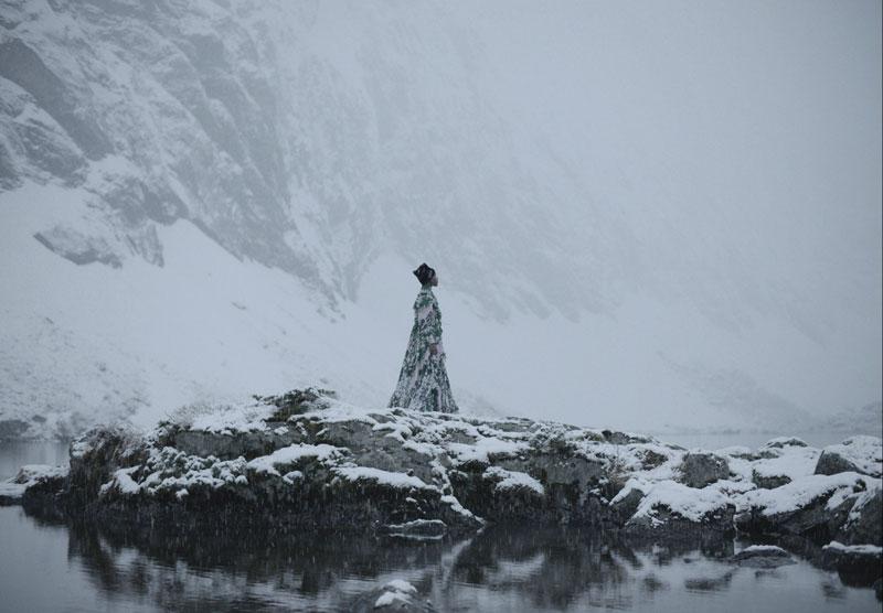 a woman in long white coat in showy mountain scene