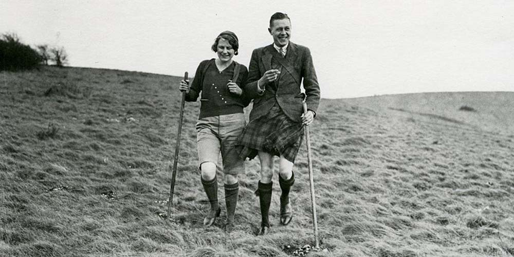 photo of a man wearing a kilt and tweed jacket smoking a fag arm in arm with a woman in shorts walking across a hillside