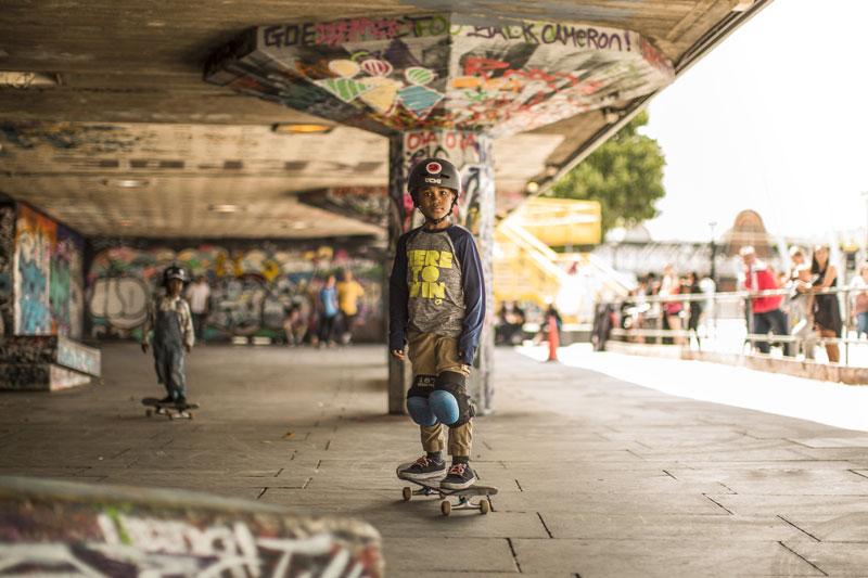 child on skateboard in graffitied skatepark