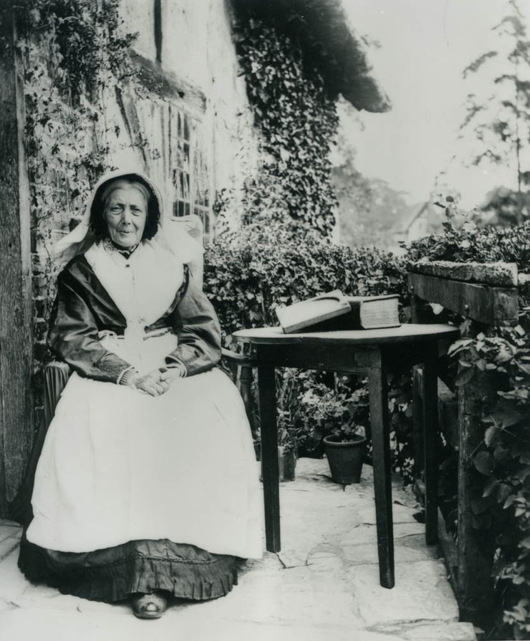 black and white photo of an elderly woman in victorian dress and cap outside a cottage