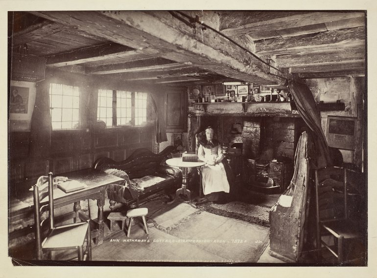 photo of an elderly woman seated in a beamed cottage interior
